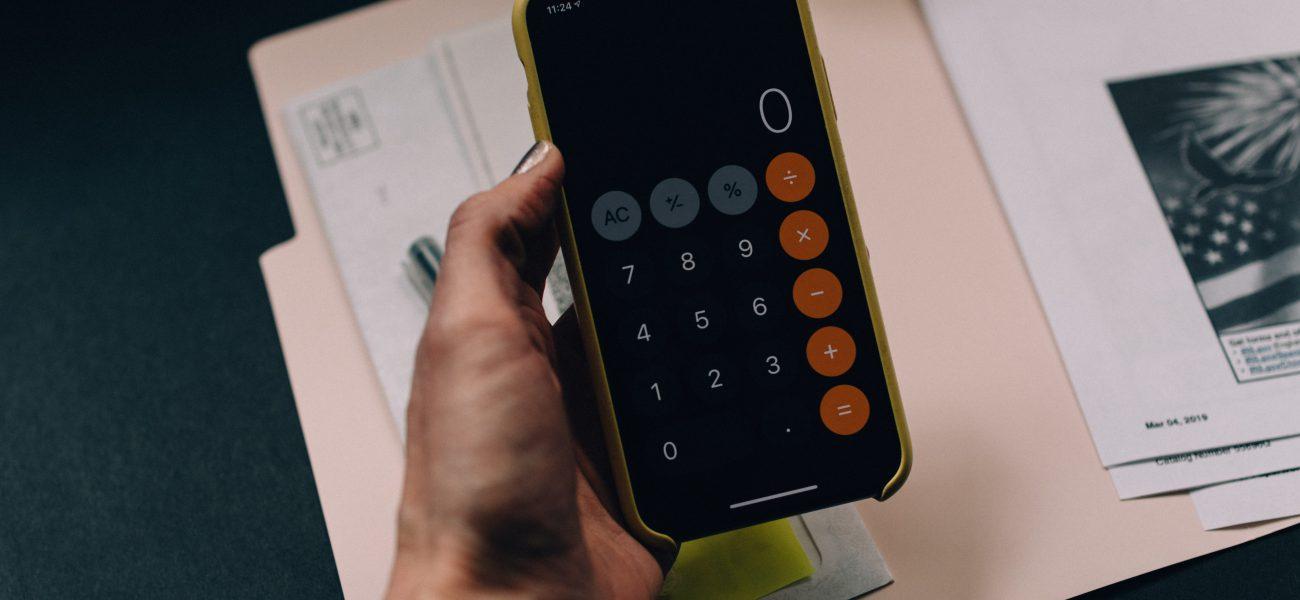 hand holding calculator symbolising tax