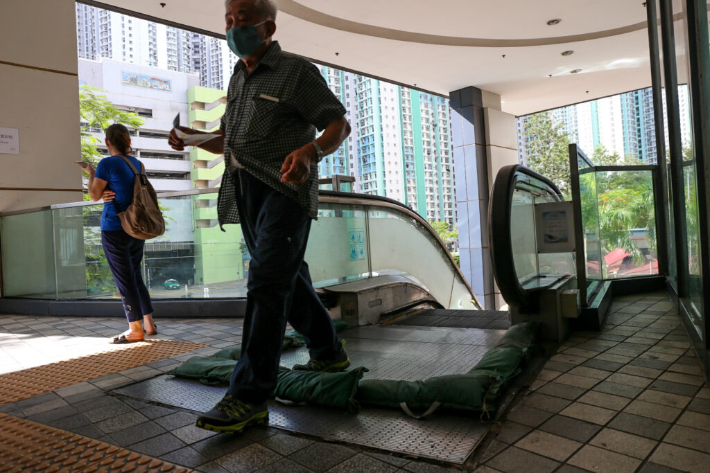 On the western side of Hong Kong's New Territories in Yuen Long, a man steps over sandbags protecting a mall escalator following a typhoon warning. Flooding is common in this low-lying area during typhoon season. This is in part due to the removal of mangrove forests directly to the north, where the high-rise buildings meet the wetlands at the head of Deep Bay. (Image: Katherine Cheng / China Dialogue)